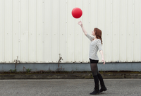 Young Woman Playing with Red Balloon Outdoors