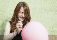 Young Woman Popping Balloon