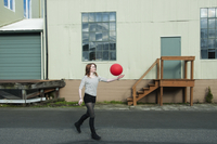 Young Woman Playing with Red Balloon in Street