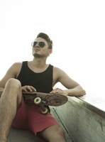 Young man sitting on cement ramp outdoors, wearing sunglasses and holding skateboard, Germany