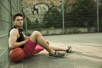 Portrait of young man sitting on ground with bsketball, at fenced-in basketball court, Germany