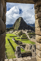 Looking through stone, structural opening at overview of Machu Picchu, Peru