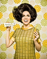 Woman in 1960's dress against 1960's flower wallpaper holding a toothbrush and tube of fictional toothpaste with a big smile and