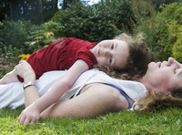Young Girl Lying on top of her Mother in the Grass, Portland, Oregon, USA