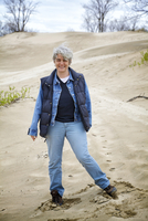 Mature woman standing on dunes at Sandbanks Provincial Park, Prince Edward County, Ontario, Canada