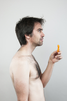 Close-up portrait of man holding cheesie in hand, studio shot on white background
