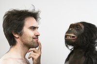 Close-up of mature man looking at toy chimpanzee, studio shot on white background
