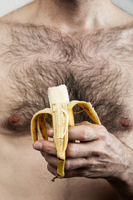 Close-up of mature man with hairy chest holding a banana, studio shot