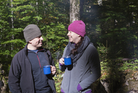 A couple camping and drinking coffee outside, Devil's Tombstone Campground in Autumn, Catskills, New York, USA