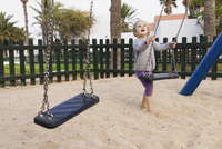 Three year old girl playing in playground with swings, Spain