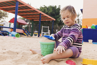 Three year old girl playing in playground with a shovel and bucket in sand, Spain