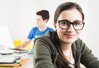 Teenage girl wearing eye glasses and looking at camera, with teenage boy working on project using computer in background, studio