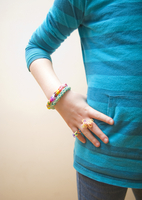 Close-up of a 7 year-old girl wearing craft bracelets and rings made from colourful rubber bands.