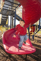 Portrait of excited little boy standing at bottom of playground slide, USA