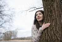 Portrait of Young Woman by Tree Trunk, Mannheim, Baden-Wurttemberg, Germany