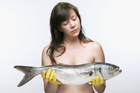 Woman wearing yellow, rubber gloves holding a bluefish, studio shot on white background