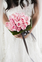 Close-up of Bride holding Bouquet of Roses
