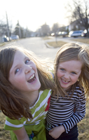 Two Sisters Playing and Laughing Outdoors in Front Yard in Springtime, Toronto, Ontario, Canada