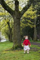 Little girl wearing red sweater, walking in park, Oregon, USA