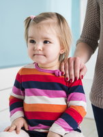 Baby Girl with Mother's Hand on Shoulder in Doctor's Office