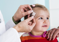 Doctor putting Bandage on Baby Girl's Head in Doctor's Office