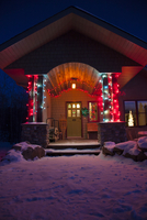 Snowy home entry with festive lights at night, Alberta, Canada.