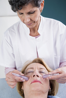 Doctor doing Crystal Therapy on Senior Patient in Doctor's Office