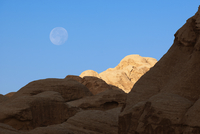 Rock formations and moon in early morning sky, Petra, Jordan