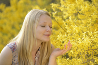 Portrait of Young Woman Smelling Forsythia Flowers in Park in Spring, Franconia, Bavaria, Germany