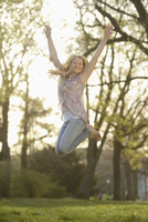 Close-up of Young Woman Jumping in the air in Park in Spring, Franconia, Bavaria, Germany
