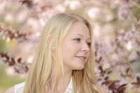 Portrait of Young Woman in front of Cherry Blossoms in Park in Spring, Franconia, Bavaria, Germany