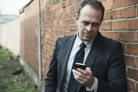 Portrait of businessman standing next to brick wall outdoors, looking at cell phone, Germany