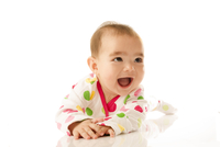 Close-up portrait of baby girl smiling, studio shot on white background