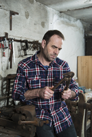Mature Man in Workshop with Tools