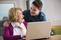 Teenage boy with grandmother working on notebook computer, Germany