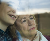 Close-up portrait of teenage grandson with grandmother looking out window together, Germany