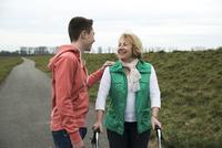 Teenage grandson talking to grandmother using walker on pathway in park, walking in nature, Germany