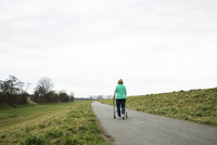 Backview of senior woman walking along path using walker in nature, Germany