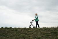 Senior woman walking along path using walker in nature, Germany