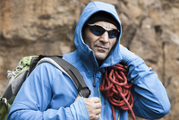 Close-up portrait of man wearing jacket and sunglasses carrying rock climbing gear, Germany