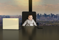 Digitally Generated Image of Baby Girl CEO sitting at Desk in Office overlooking New York City, New York, USA