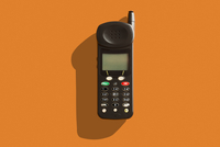 Close-up of old, cell phone from the 1990's, studio shot on orange background