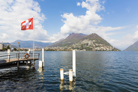 Swiss flag at a landing stage in front of Monte Bre at the promenade in spring, Lago Lugano, Switzerland
