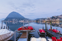 Moored pedal boats by the promenade in front of Monte San Salvatore and city lights at Lago Lugano at dawn in spring, Lugano, Sw