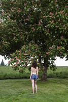 Young Woman Standing in front of Flowering Chestnut Tree, Oregon, USA
