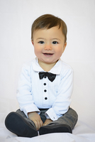 Portrait of seven month old baby boy, elegantly dressed with shirt and bow tie, studio shot on white background