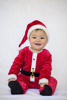 Portrait of seven month old baby boy dressed-up like Santa Claus, smiling and looking at camera, studio shot on white background