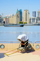 Traditional rickshaw along the Pudong promenade and 1920's Colonial Buildings across the Huangpu River on The Bund, Shanghai, Sh
