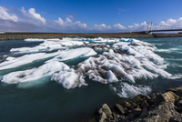 Scenic view of ice and glacial lake water with Glacial River Bridge in background, Jokulsarlon, Iceland