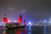 Chinese Junk in Victoria Harbor with Skyline in the background at Night, Hong Kong, China